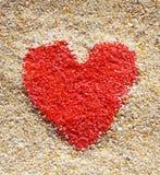 Röd hjärta undertecknar in gul sand royaltyfria bilder