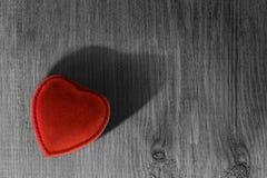 Röd hjärtaask på en trätabell arkivbild