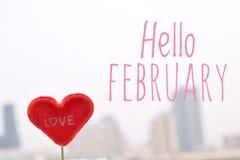 Röd hjärtaform med Hello Februari text i stadssiktsbakgrund Arkivbild