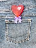 Röd hjärtaform med pilbågen i grov bomullstvillfack Royaltyfri Foto