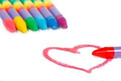 Röd hjärtaform och kulöra chalks Arkivbild
