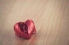Röd hjärtaform på den Wood tabellen Royaltyfria Bilder