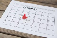 Röd hjärtaform som förläggas på 14th det februari datumet av kalendern Arkivfoto