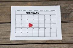Röd hjärtaform som förläggas på 14th det februari datumet av kalendern Arkivbilder