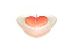 Röd hjärtaformstearinljus i den isolerade glass krukan Arkivfoton