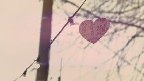 Röd hjärtagarnering som hänger på ett rep med ljus som är utomhus- Begrepp för dag för valentin` s Beröm av förälskelse arkivfilmer