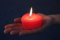 Röd hjärtastearinljus i en hand mörk lampa Arkivbild