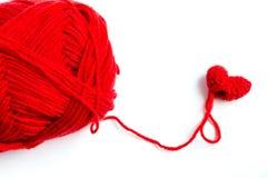 Röd hjärtavirkning med garn på vit bakgrund Arkivbild