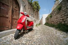 Röd italiensk sparkcykel arkivbild