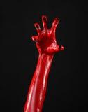 Röd jäkels händer med svart spikar, röda händer av Satan, allhelgonaaftontema, på en svart bakgrund som isoleras Royaltyfri Foto