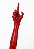 Röd jäkels händer med svart spikar, röda händer av Satan, allhelgonaaftontema, på en vit bakgrund som isoleras Arkivfoto