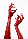 Röd jäkels händer med svart spikar, röda händer av Satan, allhelgonaaftontema, på en vit bakgrund som isoleras Royaltyfri Foto