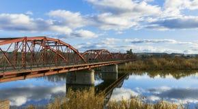Röd järnbro på en flod med blå himmel och vita moln royaltyfri foto