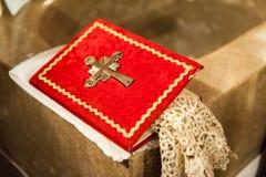 Röd järnekbok med metallkorset i kyrka arkivbilder