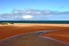 Röd jordad en kontakt bred flodmynning och hav på Carnarvon Royaltyfri Fotografi