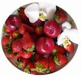 Röd jordgubbe med orkidén på den vita plattan royaltyfri bild