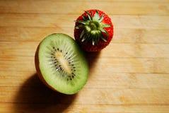 Jordgubbe och kiwi på skärbräda Fotografering för Bildbyråer