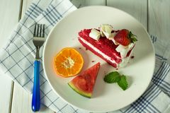 Röd jordgubbekaka som förläggas på plattan royaltyfri fotografi