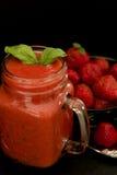 Röd jordgubbesmoothie i kruset royaltyfria bilder