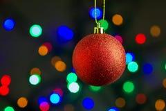 Röd jul klumpa ihop sig att hänga på guld- band med färgrik bokehbakgrund Royaltyfria Bilder