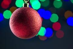 Röd jul klumpa ihop sig att hänga på guld- band med färgrik bokehbakgrund Royaltyfri Foto