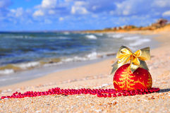 Röd jul klumpa ihop sig med den guld- pilbågen på sanden Royaltyfri Fotografi