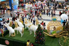 Röd jul klumpa ihop sig ovanför polystyrenstatyn av vita enhörninghästar som drar den guld- sfäriska vagnen arkivfoton