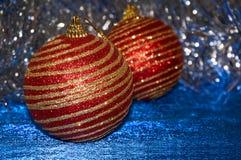 Röd jul leker med guld- band på en blå bakgrundsnärbild nytt år för bakgrundsjul Fotografering för Bildbyråer