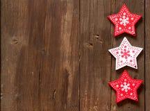 Röd jul och vita stjärnor på träbakgrund Royaltyfri Bild