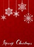 Röd julbakgrund med hängande snöflingor. Arkivfoton