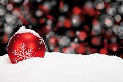 Röd julboll i snow royaltyfri fotografi