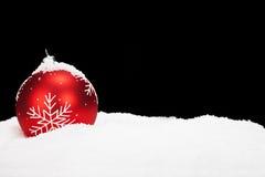 Röd julboll i snow royaltyfria bilder