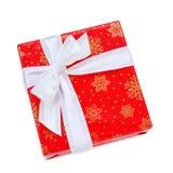 Röd julgåva med den vita pilbågen och isolerat band Arkivbild