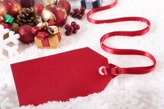 Röd julgåvaetikett som lägger på snöbakgrund med olika gåvor och garneringar Arkivbild