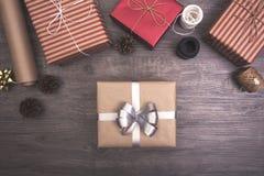 Röd julklappgåva och dekorerat lantligt lagt på trätabellbakgrund Fotografering för Bildbyråer