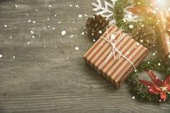 Röd julklappgåva och dekorerat lantligt lagt på trätabellbakgrund Royaltyfri Bild