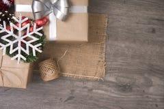 Röd julklappgåva och dekorerat lantligt lagt på trätabellbakgrund Arkivfoto