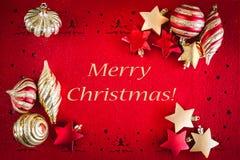 Röd julkortbakgrund med bollar, stjärnor och band och önskatext fotografering för bildbyråer