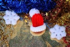 Röd jultomtenhatt i ett miniatyrslut upp på skinande guld- bakgrund med festliga garneringar Royaltyfri Bild