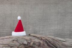 Röd jultomtenhatt på stammen för jul - wood bakgrund för en gre arkivfoto