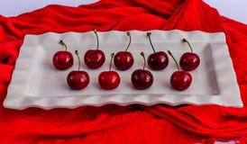 Röd körsbärsröd frukt på en vit porcelan platta Arkivfoto