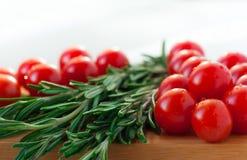 Röd körsbärsröd tomat och rosmarin på skärbräda Arkivbilder