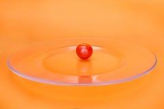 Röd körsbärsröd tomat på den genomskinliga plattan Arkivfoton