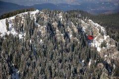Röd kabelbil över skogen som täckas med snö Arkivfoton