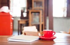 Röd kaffekopp med anteckningsboken på trätabellen Royaltyfria Foton