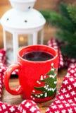 Röd kaffekopp med stearinljuset och gran på bakgrunden Royaltyfri Fotografi