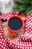 Röd kaffekopp med stearinljuset och gran på bakgrunden Arkivbilder
