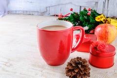Röd kaffekopp och röd gåvaask med julgranen på vit Bac royaltyfri bild