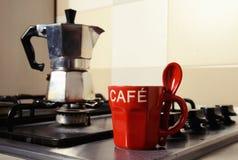 Röd kaffekopp och kaffekanna på kökugnen Arkivbild