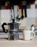 Röd kaffekopp och tappningkaffekanna på kökugnen Arkivfoto
